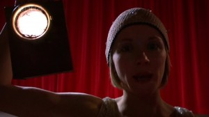 Pearl in the theater, holding up a light