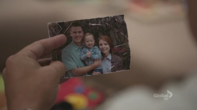 A screenshot from the TV show Bones: a wrinkled photograph of a victim and his wife and son.