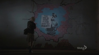 """A screenshot from the TV show Bones: Graffiti on a wall with a police officer holding a paper reading """"You have no right to take away our right."""""""