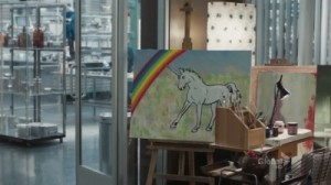 A screenshot from the TV show Bones: on an easel sits a painting of a unicorn with a rainbow behind it.