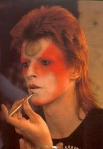 David Bowie applying his Ziggy Stardust make-up, dramatic swaths of red and white