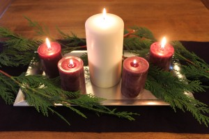 Tray with evergreen boughs, a large white pillar candle, and four smaller red candles, all lit