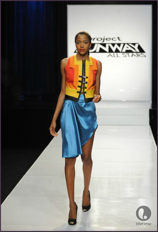 Project Runway All Stars 2x04 designer Joshua's model is wearing an asymmetrical, bright colored, shiny skirt with a bold, geometric jacket in contrasting colors.