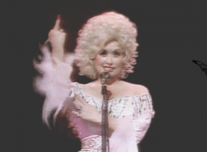 Dolly Parton with middle finger upraised and a huge smile on her face
