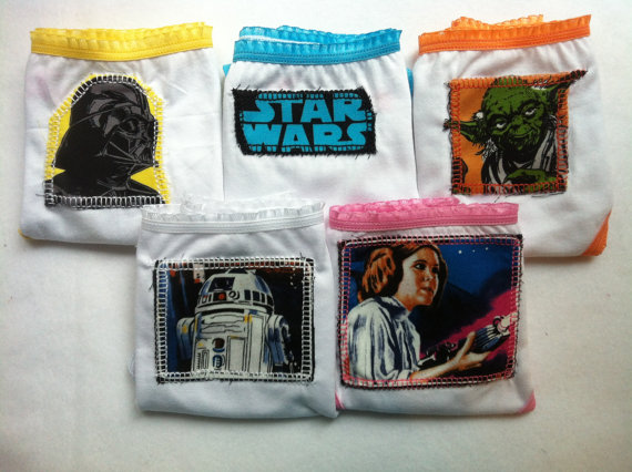five pairs of white girls underwear; one with Darth Vader, one with Star Wars logo, one with Yoda, one with R2D2 and one with Leia