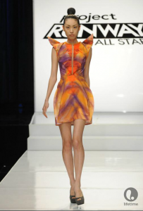Project Runway All Star contestant Uli's dress is above-the-knee, with pointed, 3D sleeve caps. The dress is in shades of orange and purple.