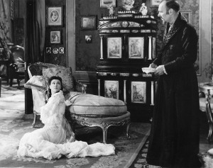 Still from Anna Karenina; Anna sits on the floor and her husband stands nearby