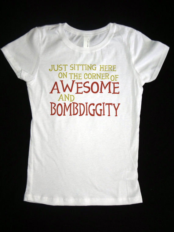 "white t-shirt that says ""just sitting here on the corner of awesome and bombdiggedy"" in red"