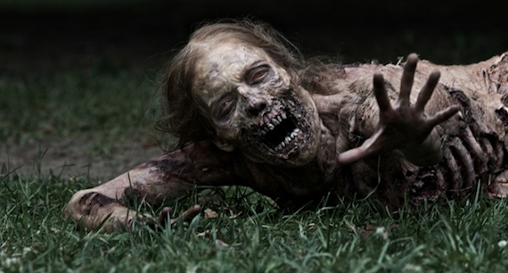 female zombie with flesh eaten away around mouth, crawling on grass with left arm outstretched