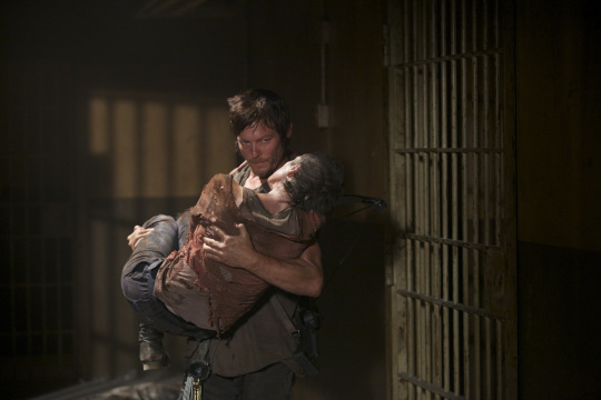Daryl carries Carol in his arms.