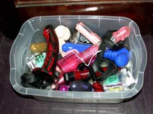 a plastic tub filled with assorted sex toys
