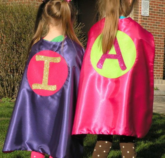 two little girls wearing capes, one is purple with a pink circle with a gold I in the middle, the other is pink with a green circle with a pink A in the middle