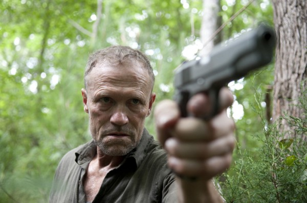 Merle in the woods, aiming a handgun