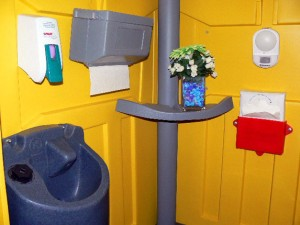 Interior of a porta-potty with a sink, soap and towel dispensers, a vase with flowers, and paper seat covers