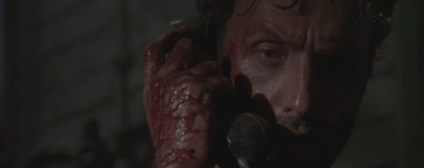Rick holds a phone to his ear with a bloody hand.
