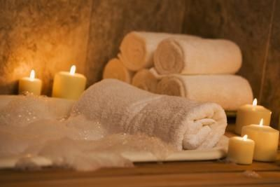 Spa tub with bubbles and surrounded by lit candles and fluffy white towels