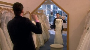 Ianto picking out a wedding dress, holding it up to look in the mirror