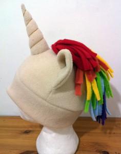 cream colored polar fleece hat with a unicorn horn and rainbow mane