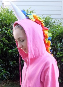 young teen girl outside in a pink hoodie with a unicorn horn and rainbow yarn mane