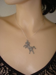close up of woman's collarbone wearing a black v-neck shirt and a black glitter shaped unicorn necklace on a silver chain