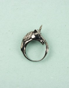 light green background, silver unicorn ring, 3-d profile that wraps around the finger