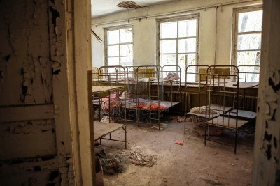 Abandoned nursery with rickety metal beds and peeling paint on the walls