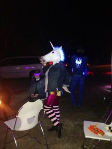 writer wearing pink leggings, legwarmers, rainbow sweater and scary unicorn mask