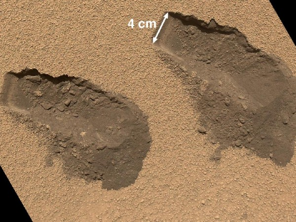 Image of the surface of Mars with two small holes scooped out, showing the dark soil beneath the lighter surface. One hole is labelled as being 4cm wide.