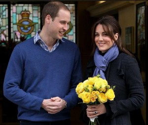 William and Catherine leaving the hospital. Both are smiling, and Kate is carrying a bouquet of yellow flowers.