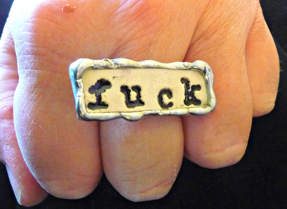 "fist wearing a gold and silver ring with the word ""Fuck"" stamped on it"