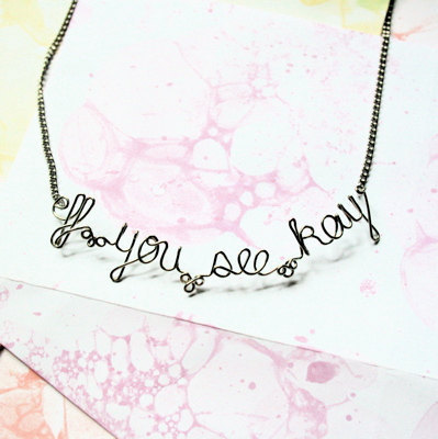 "gold colored wire necklace that says ""eff you see kay"""
