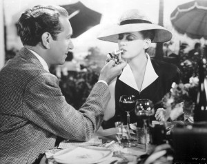 Scene from Now, Voyager; Jerry lights a cigarette for Charlotte as they sit at an outdoor restaurant table.