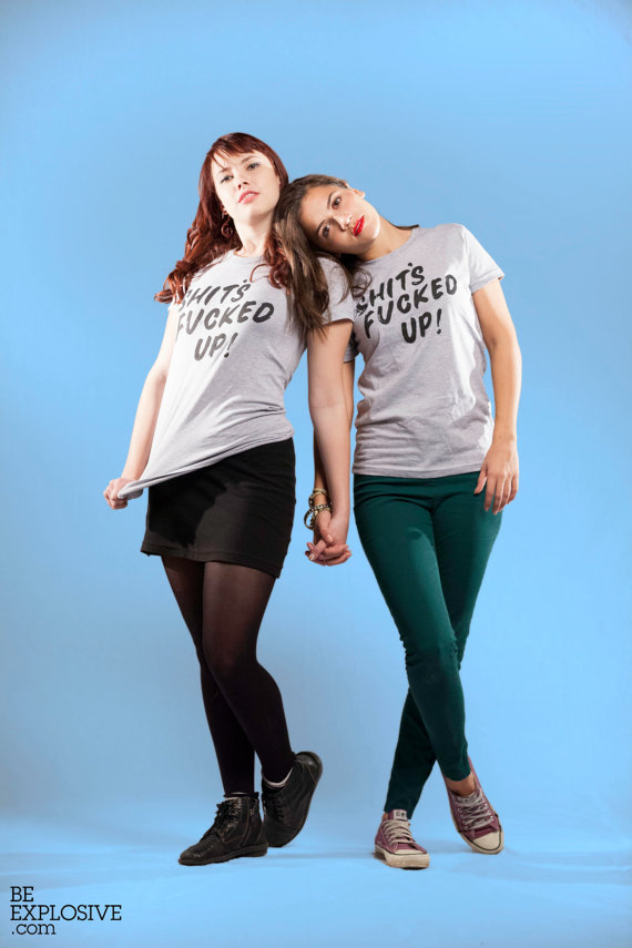 "two women holding hands wearing a grey shirt that has ""Shits Fucked Up"" printed in black"