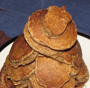 Plate heaped with acorn pancakes. The top one is shaped like an acorn.