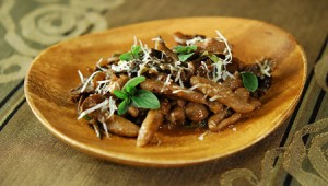 Bowl of acorn cavatelli pasta garnished with mushrooms, cheese, and fresh herbs
