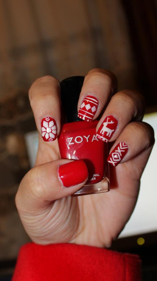Nails painted red with white designs painted on: poinsettia, stripes, and reindeer.