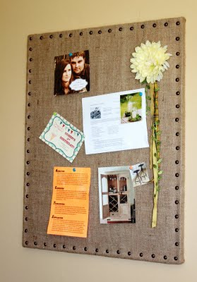 burlap covered cork board with photos, notes and a flower pinned to it.