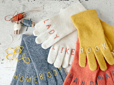 four pairs of gloves, grey, cream, yellow and salmon, with handstitched wording on the knuckles- Lady Like, Hand Made, Home Body and Book