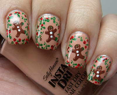 Taupe nails with a tiny gingerbread man surrounded by holly on each one. Person is holding a bottle of the base coat, Sally Hansen Insta-Dri in Quick Sand.