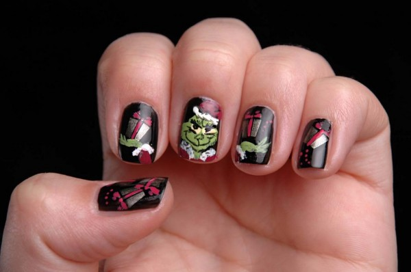 Black nails with the Grinch painted across three fingers and extra presents on the thumb and pinky