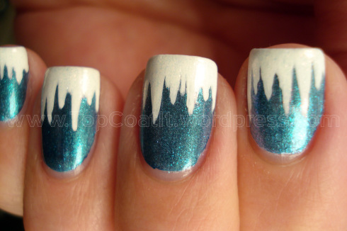 Nails painted a sparkly green-ish blue with white tips that drip down into icicles