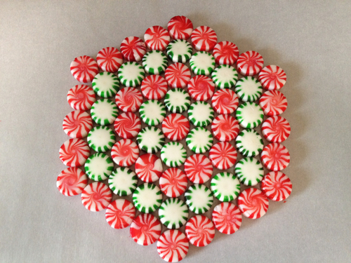 Peppermints arranged on parchment paper in a hexagonal pattern with alternating rows of red and green mints.