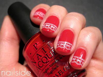 Nails painted red with a white lace pattern stamped near the tips. Person is holding a bottle of the base coat, OPI Big Apple Red.