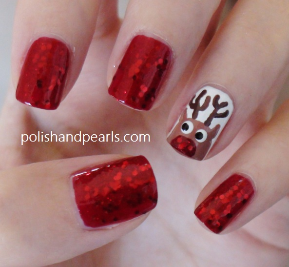 Four nails painted with red glitter, with an accent nail of Rudolph's face and antlers on a white background.
