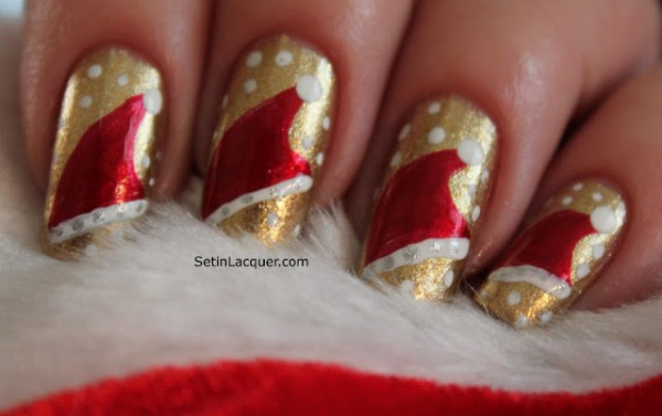 Nails painted gold with red Santa hats trimmed in white, surrounded by tiny white snowflakes
