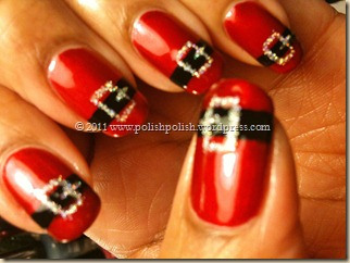 Nails painted red with a black stripe and silver glitter belt buckle