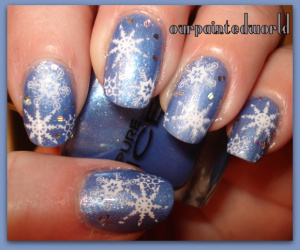 Nails painted a shimmery ice blue with white snowflakes stamped on and a hint of silver glitter