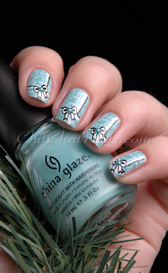 Tiffany blue nails with a white lace pattern and black and white ribbons and bows. Person is holding bottle of the base coat, China Glaze For Audrey, and a fake evergreen sprig.