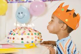 A young boy wearing an orange crown blowing out the candles on a colorful birthday cake