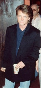 picture of a young Michael J. Fox wearing a blue button up shirt, a black sports coat and jeans, holding a cup